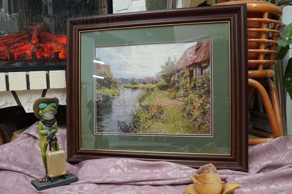 """Вышивка крестом """"Дом у реки"""" оформлена в коричневую багетную рамку с широким паспарту"""