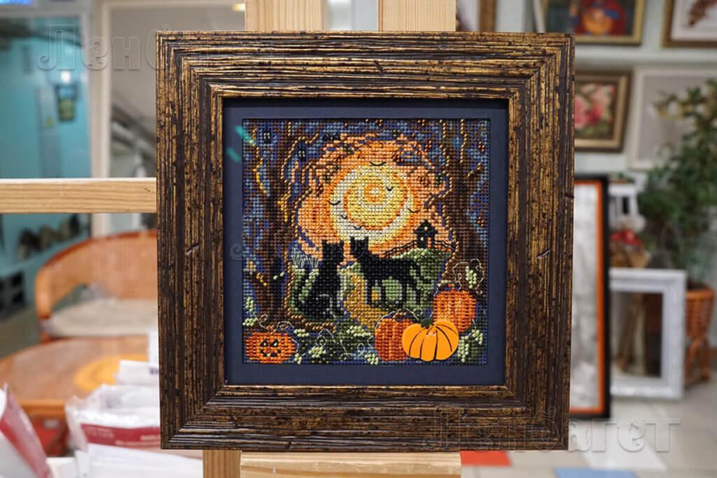 """Вышивка крестом """"Лунные хозяева"""" оформлена в коричневую багетную рамку с широким паспарту"""