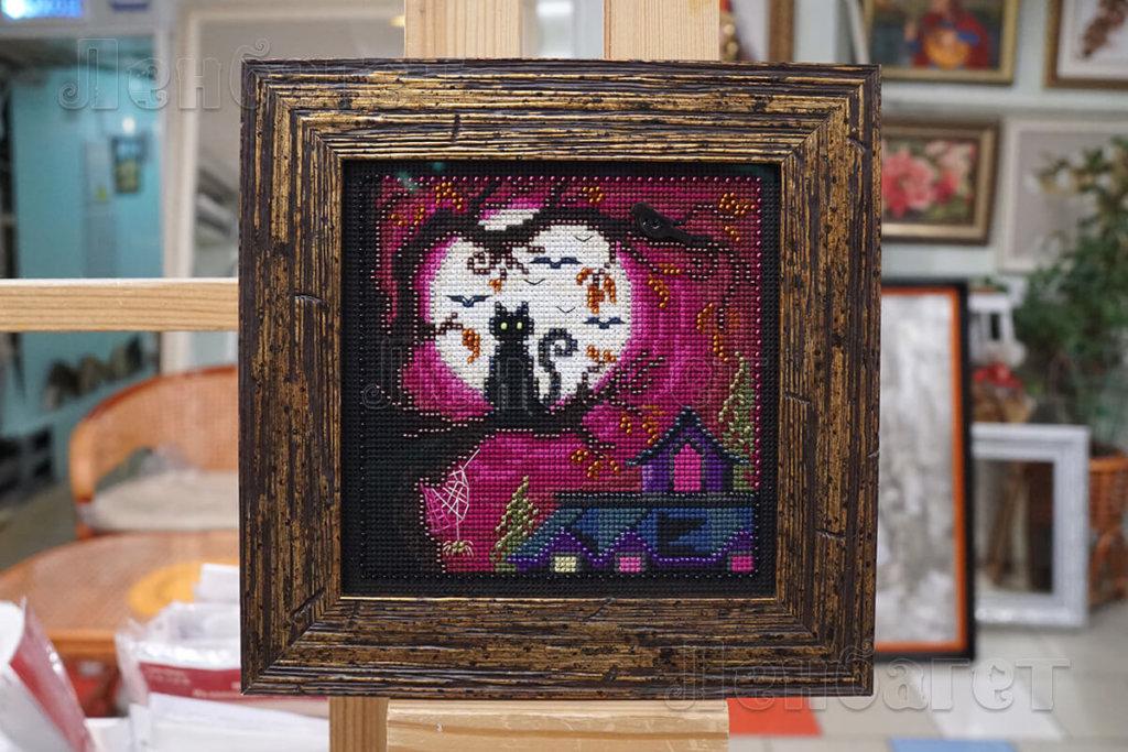 """Вышивка крестом """"Лунный кот"""" оформлена в коричневую багетную рамку с широким паспарту"""