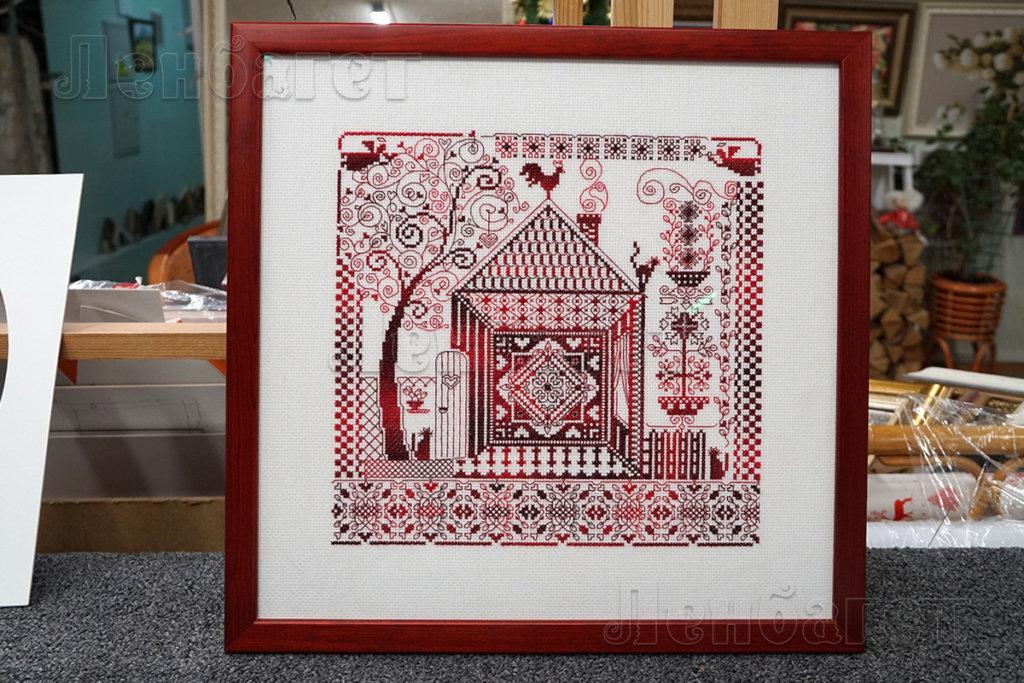 """Вышивка крестом """"Оберег домашнего очага"""" оформлена в красную багетную рамку с широким паспарту"""