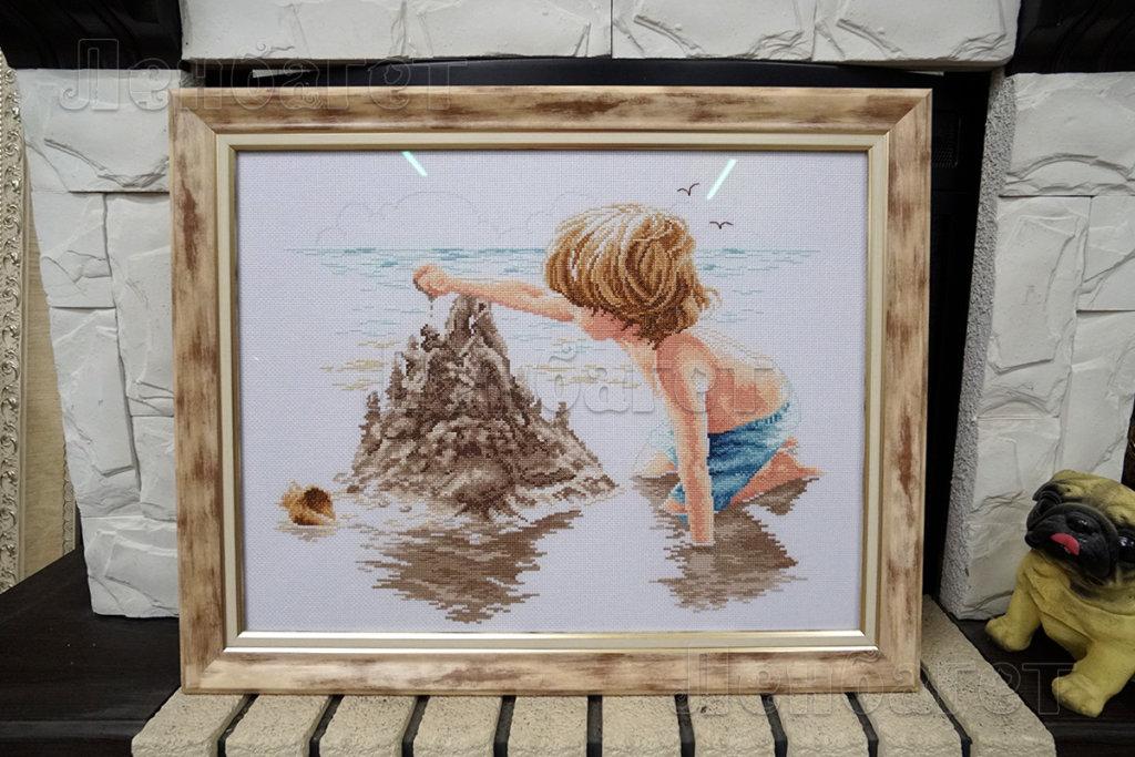 """Вышивка крестом """"Песочный замок"""" оформлена в коричневую багетную рамку"""