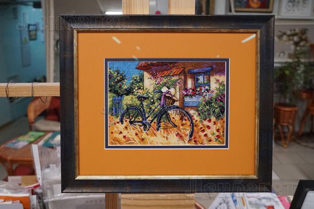 """Вышивка крестом """"Велосипед"""" в коричневой багетной рамке с двойным паспарту"""